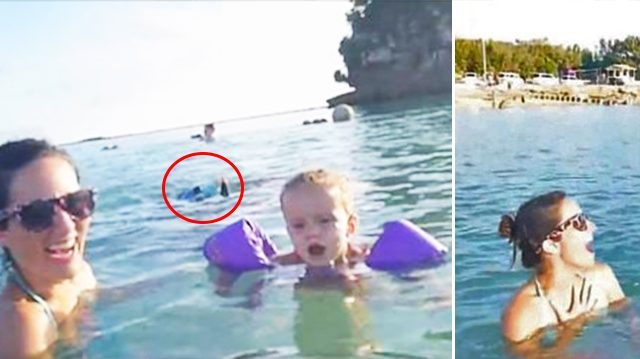 A woman and  her kids were swimming on a beach, totally unaware that 'something' was approaching them underwater