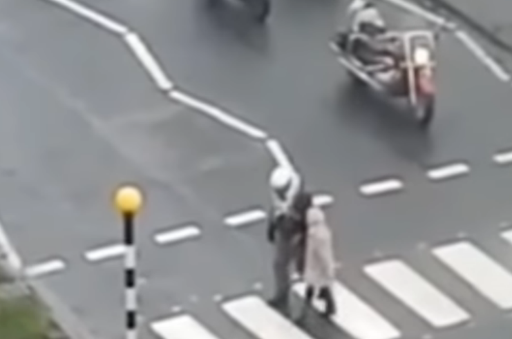 Biker helps elderly woman cross the street after cars refuse to stop